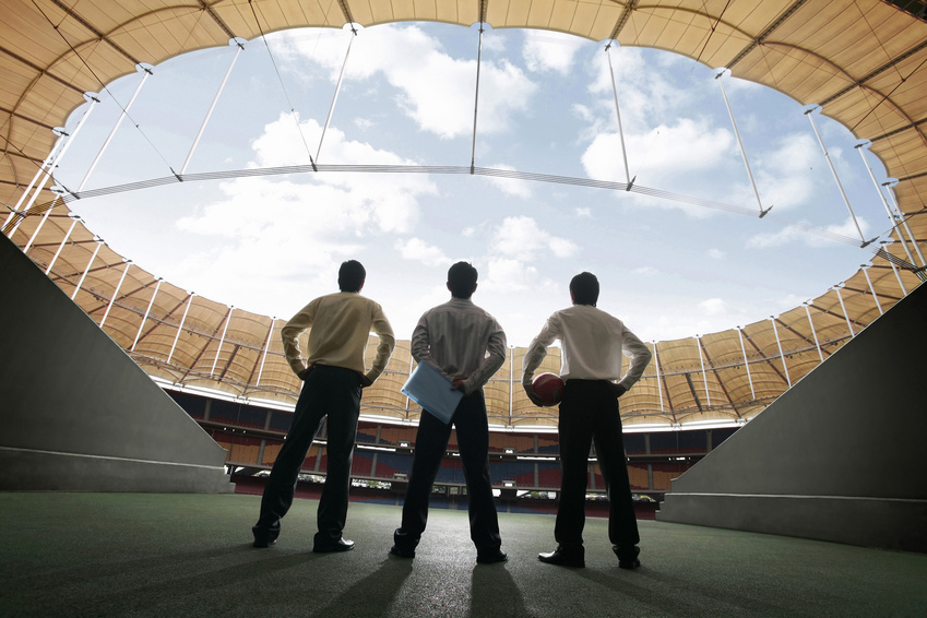 Three businessmen standing at the stadium